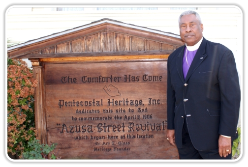 Bisho Ealy in front of Azusa Street Revival sign at Bonnie Brae House